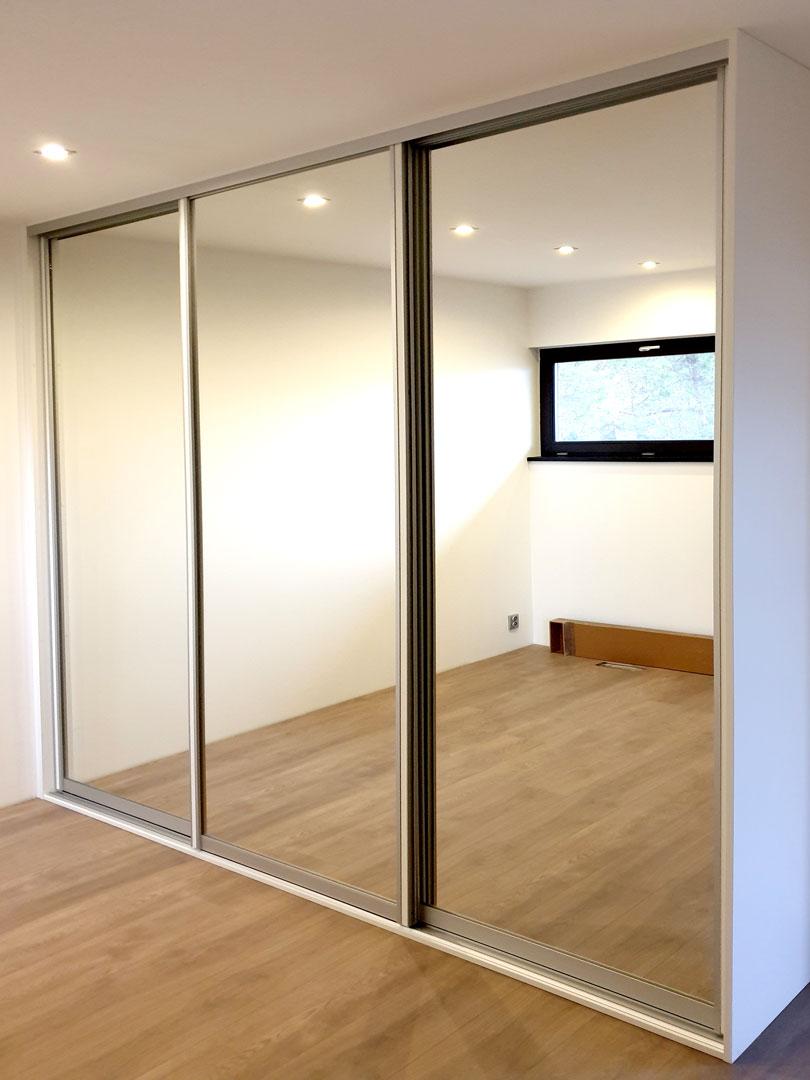 Realizace vestavěné skříně se zrcadlovými posuvnými dveřmi.