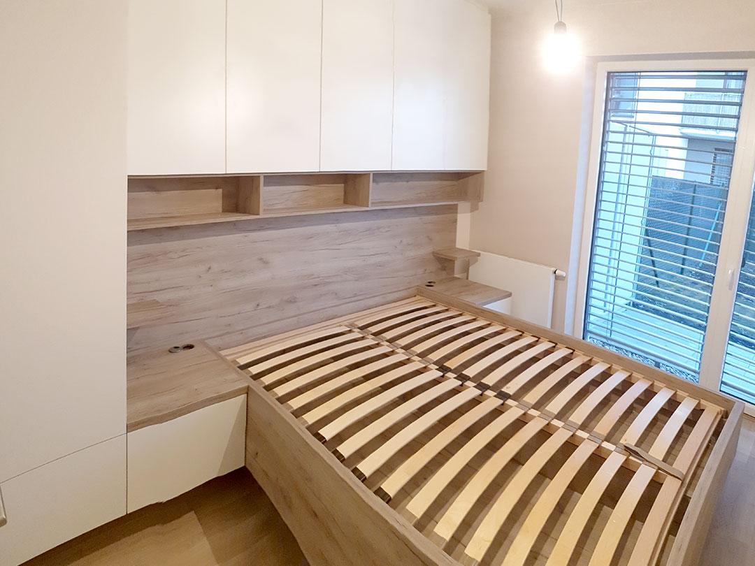 Realizace kompletního bytu. Zde ložnice s postelí a skříňkami obestavěnými kolem postele.