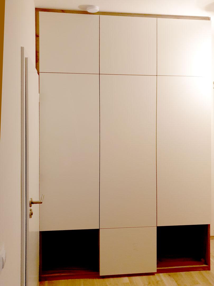 Vestavěná skříň s pantovými dveřmi v kombinaci bílých dveří a dřevěného korpusu.