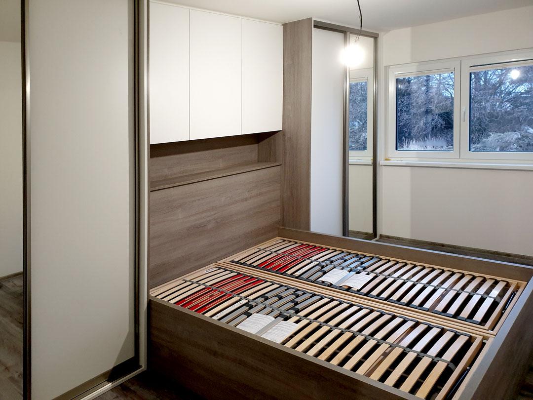 Ložnice na míru s postelí a vestavěými skříněmi v dekoru přírodní dub a krémová barva.