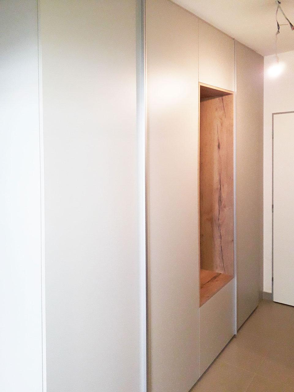 Vestavěná skříň do chodby s pantovými dveřmi a otevřenou dubovou částí s věšáky.