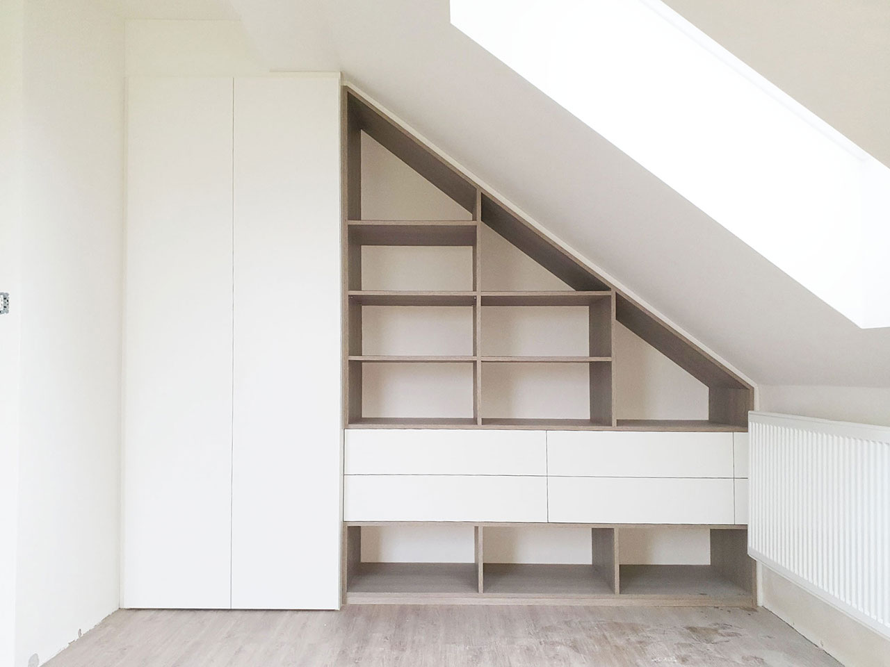 Vestavěný skříň do šikmého prostoru v bílém provedení kombinovaná s dřevěnou otevřenou částí a šuplíky