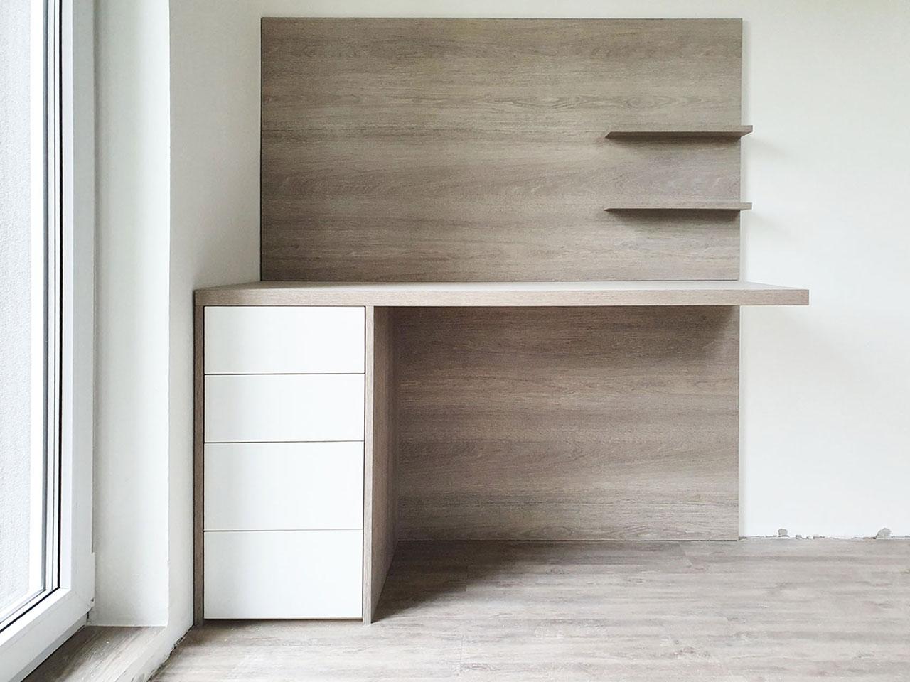 Částečně levitující pracovní stůl v dřevěném dekoru s bílými zásuvkami.