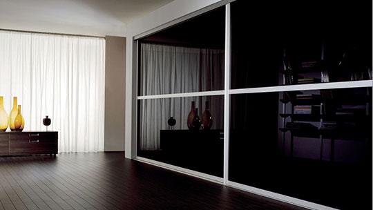 Vestavěná skříň se skleněnými posuvnými dveřmi.