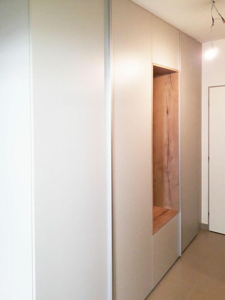 Vestavěná skříň v bílé barvě s dřevěnou otevřenou částí