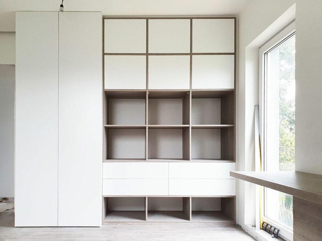 Skříň s pantovými dveřmi a šuplíky kombinovaná s otevřenými regály. Barva bílá v kombinaci se dřevem.