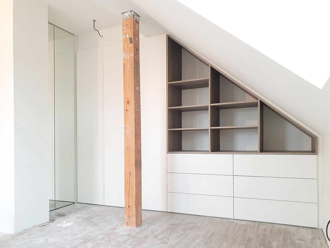 Rohová skříň na míru do podkroví. Pantové bílé a zrcadlové dveře se šuplíky a dřevěnou otevřenou částí.